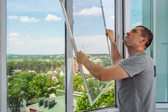 Free A Worker Installing Mosquito Wire Screen On House Plastic Windows To Protect From Insects. Royalty Free Stock Photos - 188747848