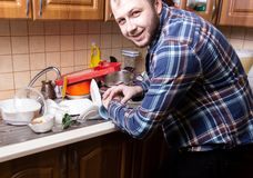 Free A Young Bearded Guy Looks At His Watch And Is Happy By The Amount Of Dirty Dishes Lying In The Kitchen Sink. He Have Time To Wash Royalty Free Stock Photos - 143037898