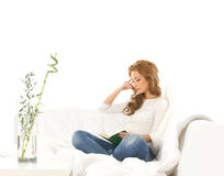 A Young Caucasian Woman Reading A Book On A Sofa Stock Photo