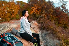 Free A Young Caucasian Woman Sits On A Stone Ledge And Admires Nature. Next To It Is A Backpack. The Concept Of Hiking And Travel Royalty Free Stock Photography - 174207557