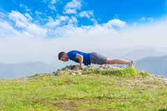 Free A Young Fit Male Athlete Is Doing Push-ups Outdoors On A Cliff While Looking At The Breathtaking Mountain Line Stock Photography - 157031382