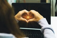 Free A Young Girl Made A Heart Sign With Her Hands Against The Background Of A Black Laptop Monitor. Communication And Love Online. A Y Stock Photo - 198555690