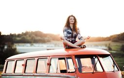 Free A Young Girl On A Roadtrip Through Countryside, Sitting On The Roof Of Minivan Doing Yoga. Stock Photo - 139215310