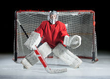 A Young Ice-hockey Goaltender In A Ready Position Against A Dark Royalty Free Stock Images
