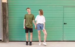 Free A Young Man And An Attractive Girl Hold Hands On A Turquoise Background And Look Into The Camera. Beautiful Young Couple Standing Royalty Free Stock Photography - 187903447