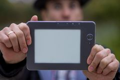 A Young Man Holds A Digital Tablet In Front Of Him Stock Image
