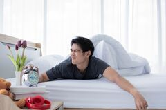 Free A Young Man Is Waking Up In The Morning While The Clock Alarms Royalty Free Stock Photo - 174907485