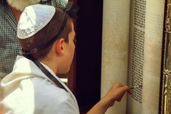 Free A Young Man Pointing At A Phrase In A Bible Book Sefer Torah, Bible Book, While Reading A Pray At A Jewish Ritual Stock Image - 116998721
