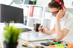 A Young Man With Glasses And Headphones Stands Near A Computer Desk. A Young Man Draws A Marker On A Magnetic Board. Royalty Free Stock Image