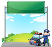 A Young Policeman With His Police Car Near An Empty Signage Royalty Free Stock Images