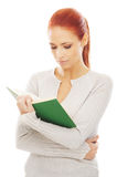 A Young Redhead Woman Reading A Book Royalty Free Stock Images