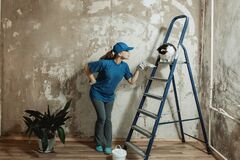 Free A Young Woman In A Blue T-shirt And A Baseball Cap Makes Repairs In The Apartment. Stock Photo - 177842430