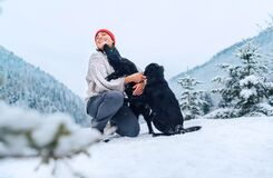 Free A Young Woman In Warm Clothes Walking Her 2 Dogs In A Picturesque Snowy Mountain Outdoor. Female Laughing And Playing With Pets Royalty Free Stock Image - 210234776