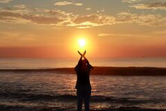 Free A Young Woman Silhouette Raising Her Hands Towards The Sky And Standing On The Sea Shore At Sunrise In The Morning, Welcoming And Stock Image - 197341041