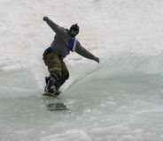 A043 Pond Skimming. Snowboarder skims water obstacle closing day at ski resort Royalty Free Stock Photos