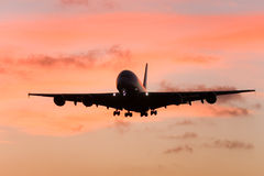 A380 airliner approaching landing at sunset. Silhouette of A380 airliner in flight at sunset Stock Photos