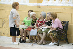 有藤茎的老妇人在长凳谈话在南西班牙的村庄在塞维利亚西部的高速公路A49 免版税库存图片