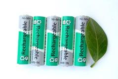 AA-Batterien und ein grünes Blatt. Stockfotos