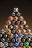 AA batteries. Many different colored AA batteries arranged in a pyramid on a dark gradient background Stock Image