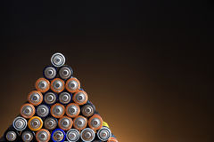 AA batteries. Many different colored AA batteries arranged in a pyramid on a dark gradient background Royalty Free Stock Photos