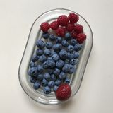 A succulent glass dish of berries - RAW VEGAN. AA berry is a small, pulpy, and often edible fruit. Berries are typically juicy, rounded, brightly colored, sweet Stock Photos