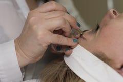 AA-Frau an der Aufnahme an einem Cosmetologist leitet Manipulationen auf der Haut des Gesichtes Lizenzfreie Stockbilder