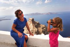 Aa-lilla flickan tar bilder av hennes moder mot de härliga sikterna av Santorini fotografering för bildbyråer