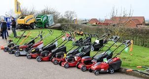 A row of red lawn mowers. Aa row of red lawn mowers on sale for cutting lawn grass and doing chores and home maintenance Royalty Free Stock Photography