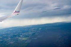 AA tipo vermelho e azul de COM na asa de aviões acima da nuvem Fotografia de Stock Royalty Free