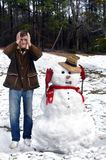 Aaahhh!  I'm Melting!. Snowman and young man put their hands to their heads.  Snowman is lamenting the snow melting Stock Photography