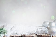 Aabstract christmas background with silver baubles and fir on empty snowy table royalty free stock photo
