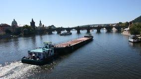 Aak en Sleepbootvrachtschip die Vltava-rivier varen dichtbij Charles Bridge stock video