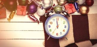 Aalrm时钟在圣诞节玩具附近的一条围巾 免版税库存照片