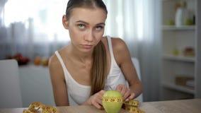 Aan anorexie lijdend meisje die appel met band meten, die calorieën en de index van de lichaamsmassa tellen stock afbeeldingen