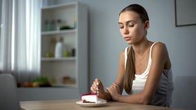 Aan anorexie lijdend meisje die cake, onvermogen proberen te eten om voedsel te verteren, gezondheidsproblemen stock afbeeldingen