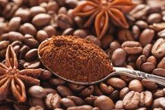 Aan de grond gezete koffie in zilveren lepel boven coffebonen Stock Foto
