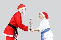 Aan de jongen in karategi geeft Santa Claus met een zwart band een drinkbeker op karate stock foto
