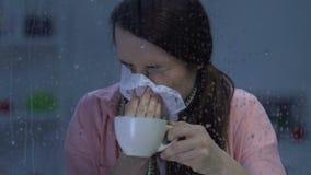 Aan griep lijden, hete drank drinken en dame die, griepepidemieën niezen stock footage
