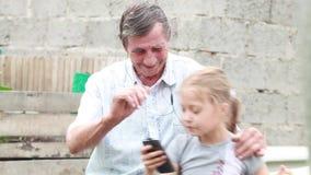 Aan muziek op hoofdtelefoons luisteren en grootvader en kleindochter die houdend een celtelefoon in het park dansen stock videobeelden