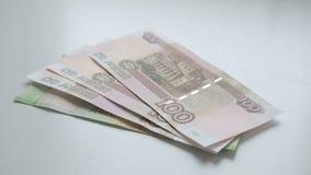 Aan tellingsgeld Gelddalingen op een witte lijst De mensenhand werpt Russische nominals 200 en 100 en muntstukken van roebelsbank stock footage