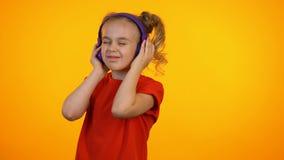 Aanbiddelijk aan muziek in oortelefoons luisteren en meisje die, favoriet lied, droom dansen stock video
