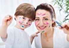 Aanbiddelijk aantrekkelijk moeder en kind het schilderen succes Stock Fotografie