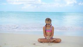 Aanbiddelijk actief meisje op een sneeuwwit zandig strand stock footage