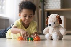 Aanbiddelijk Afrikaans jong geitje die op warm vloerspel liggen met speelgoed royalty-vrije stock foto