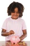 Aanbiddelijk Afrikaans meisje dat een muntstuk in een piggbank zet Stock Fotografie