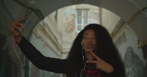 Aanbiddelijk Afrikaans meisje met mooie glimlach en lang krullend haar die selfies via de mobiele telefoon in de straat nemen 4K stock video