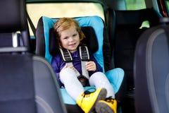 Aanbiddelijk babymeisje die met blauwe ogen in de zetel van de autoveiligheid zitten Peuterkind die op familievakanties en jorney royalty-vrije stock foto's