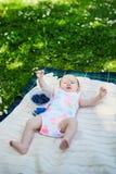 Aanbiddelijk babymeisje die op het gras op een de zomerdag liggen Royalty-vrije Stock Afbeeldingen