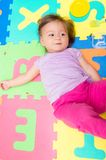 Aanbiddelijk babymeisje die op vloermatten liggen Royalty-vrije Stock Afbeeldingen
