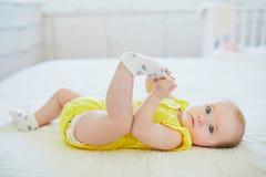 Aanbiddelijk babymeisje die sok verwijderen uit haar voet stock afbeelding